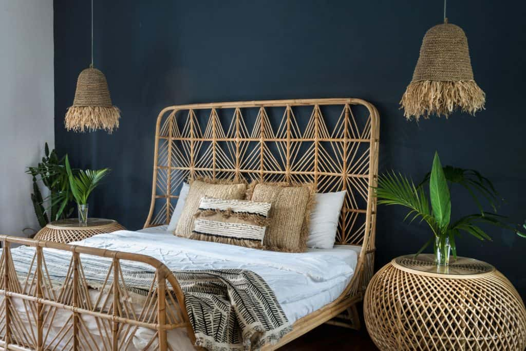 A gorgeously made rattan bed, end table, dangling lamps inside a bedroom with a blue accent wall