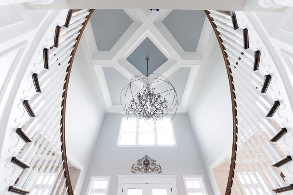 A grand white foyer with white painted stair banisters and a gorgeous blue painted coffee ceiling