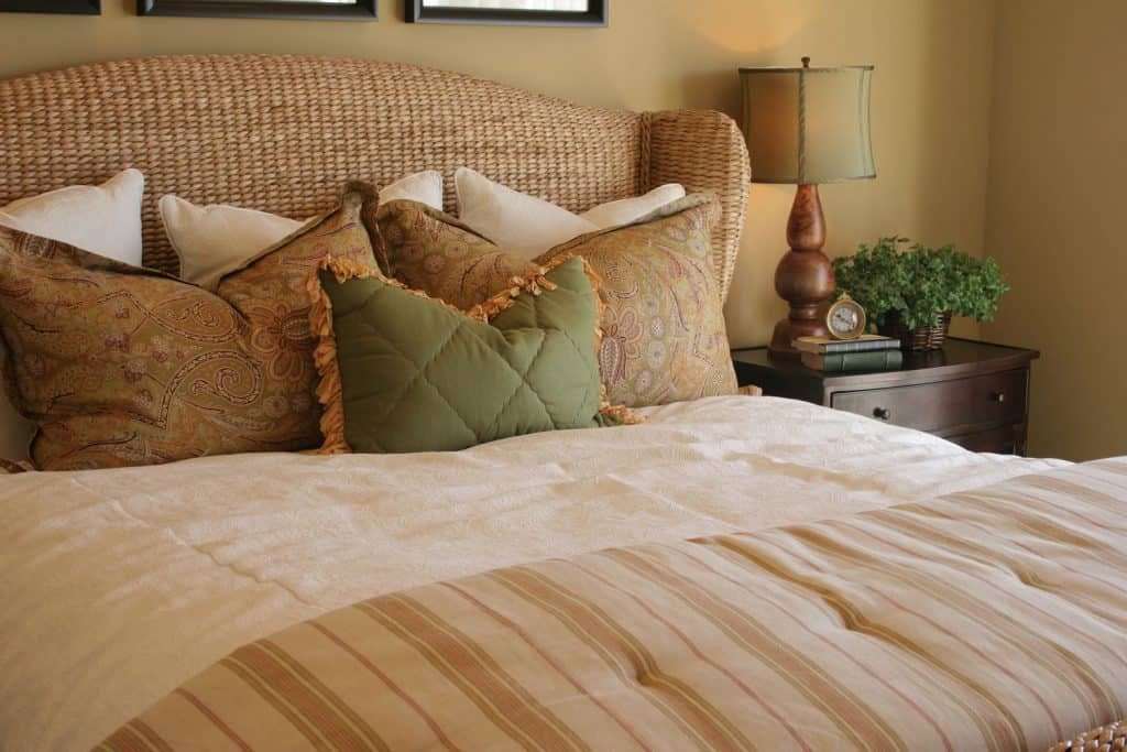 A huge rattan bed with white and brown pillows