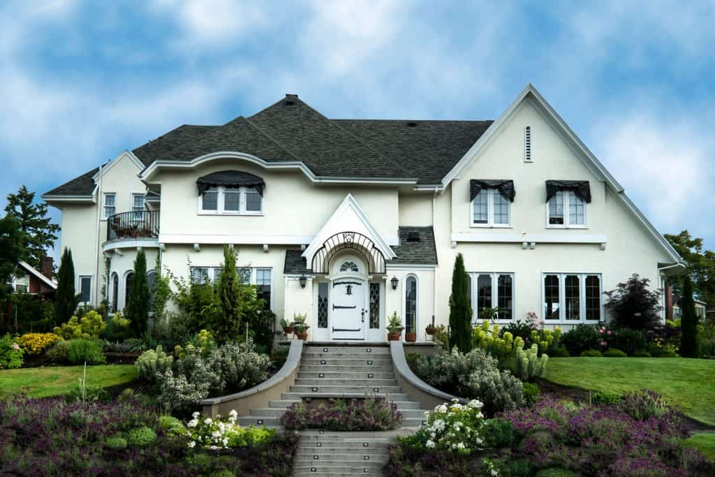 A huge two storey house with white painted exterior wall, black asphalt shingle roofing, and a gorgeous outdoor landscaping