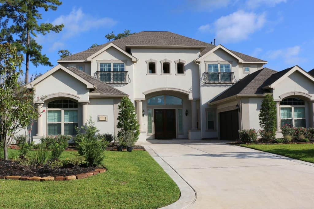 A huge two storey mansion with a stucco exterior wall, shingle roofing, and a gorgeous front lawn landscaping