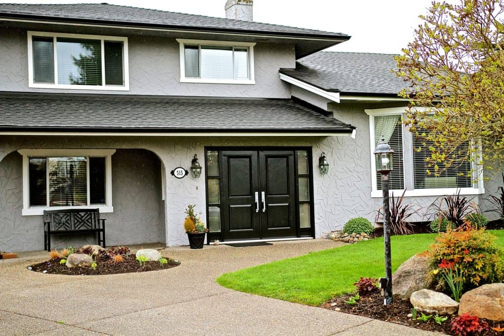 A huge two storey mansion with gray stucco wall cladding, sliding windows, and asphalt shingles