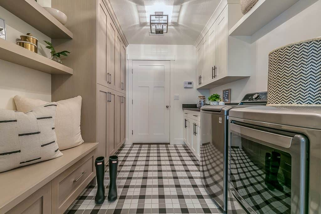 A luxurious modern interior of a washing area with checkered flooring, light cream painted walls, and a washing machine with a dryer on the side