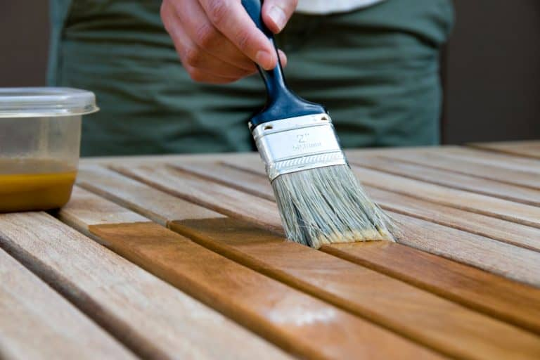A man brushing the deck with oil to make it look brand new, How To Oil Outdoor Furniture [7 Easy Steps]