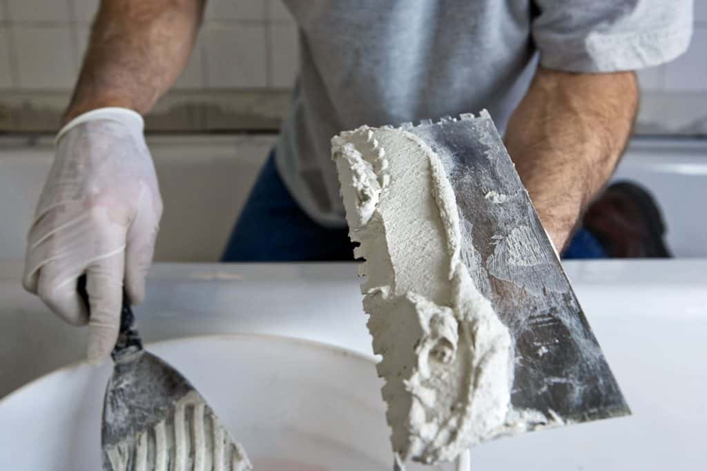 A man using a trowel to scoop tile adhesive