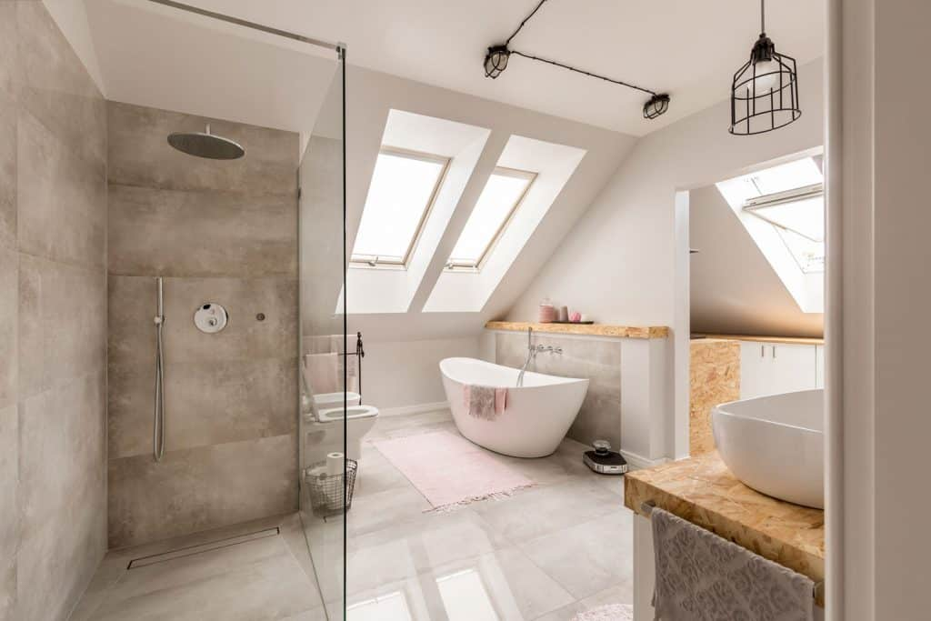 A mansard type bathroom and shower area with a glass walled shower area