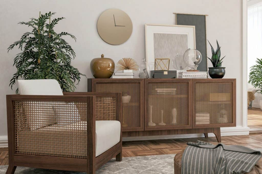 A modern Scandinavian themed living room with a wooden screened sideboard with furniture's on top