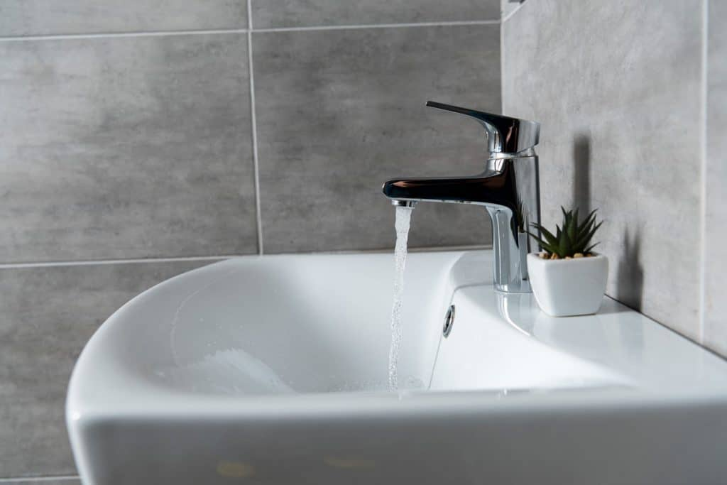 A modern bathroom sink with the water faucet turned on