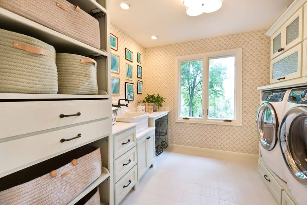 A modern beige patterned wallpaper, tiled flooring, and a twin washing machine on the sides