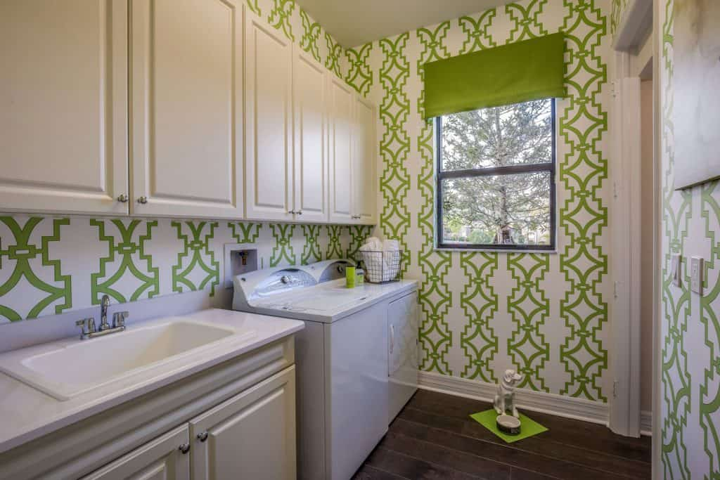 A modern laundry shop with green patterned wallpaper. white paneled cabinetry. and black wooden laminated flooring