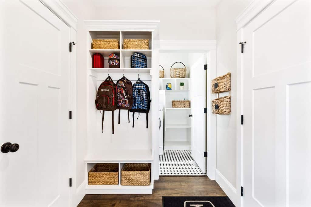 A modern white colored laundry room with bags and baskets placed on the dividers
