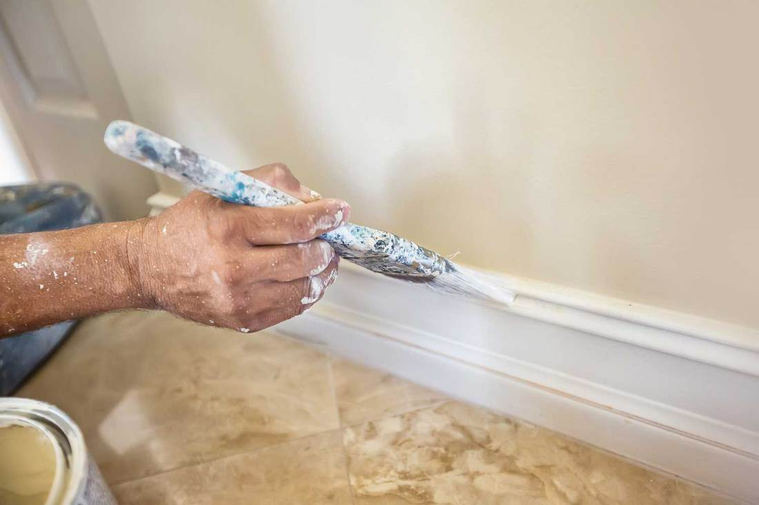A painter puts the finishing touches on the painting of a baseboard molding