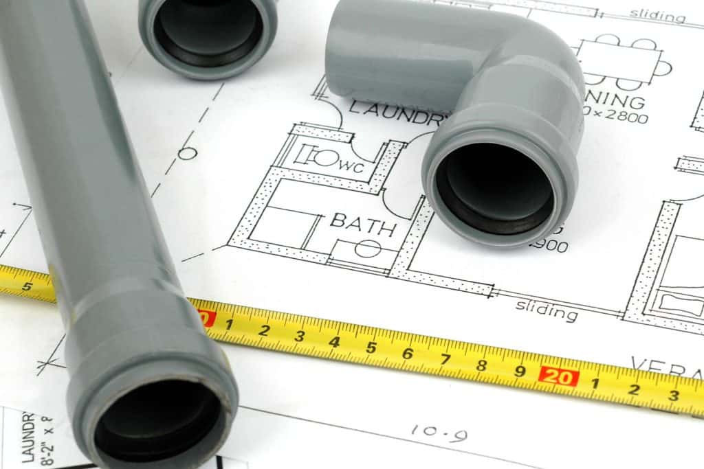 A plumbing plan of a house with PVC pipes and a measuring tape on top of a floor plan