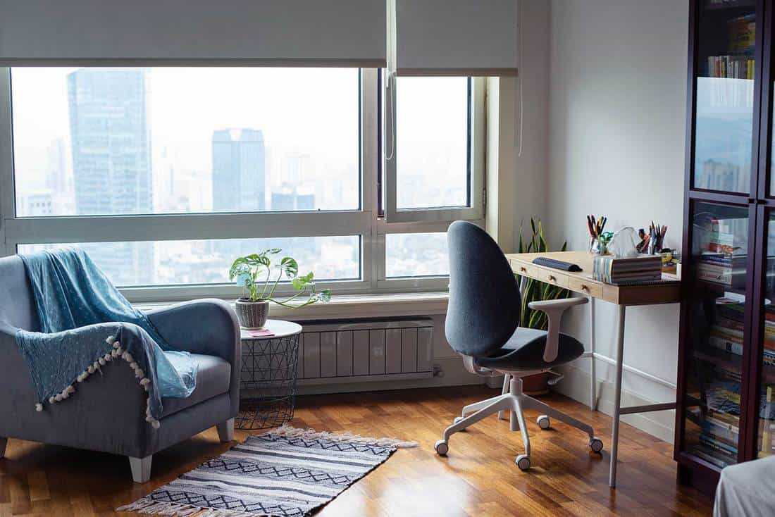 A room used as a home office with city overview on glass windows