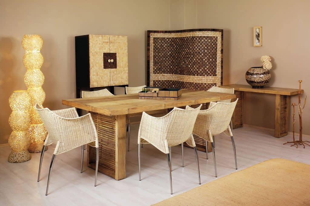 A rustic inspired living room with rattan dining chairs, wooden dining table, and brown painted walls