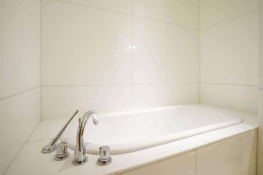 A small and white colored fitted bathtub