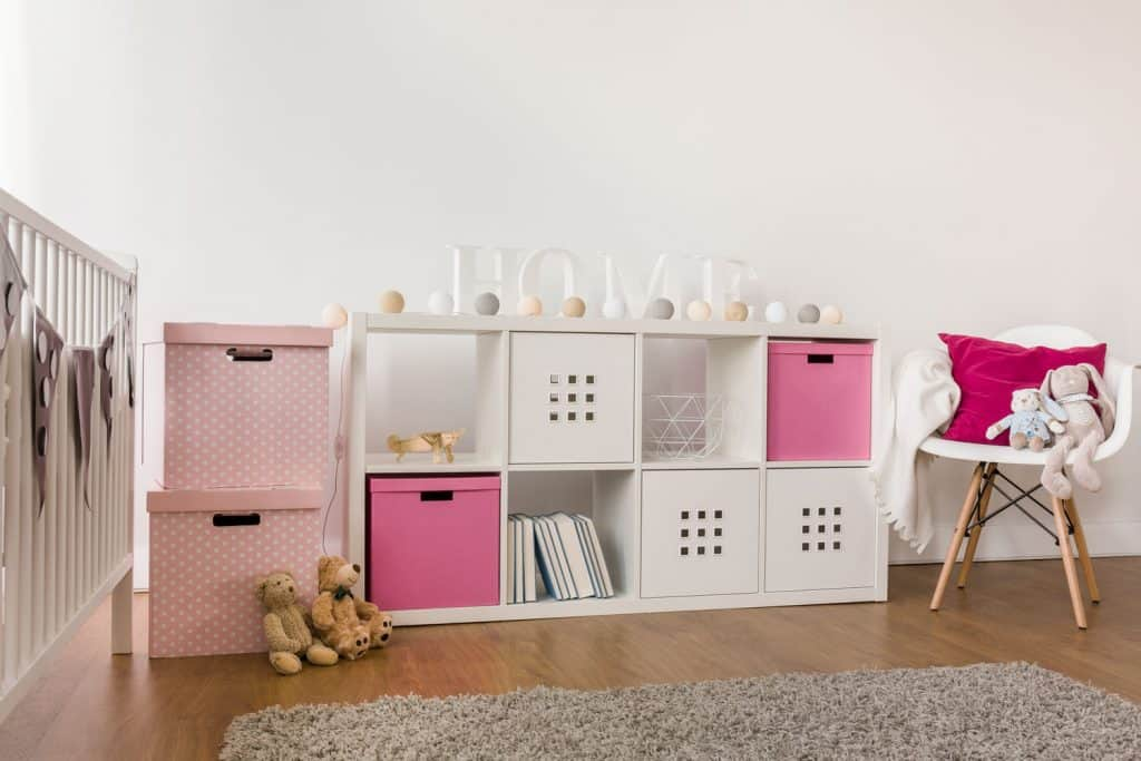 A small white sideboard with different pink colored containers, Sideboard Vs Buffet Vs Credenza - Everything You Need To Know