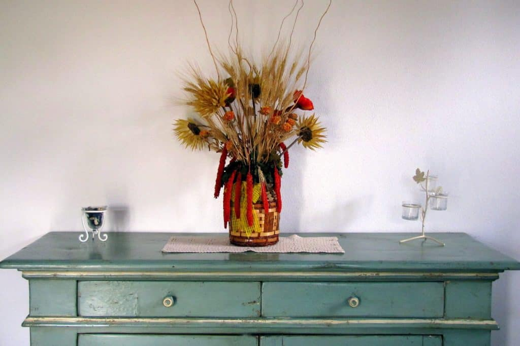 A small withered indoor plant on top of the sideboard