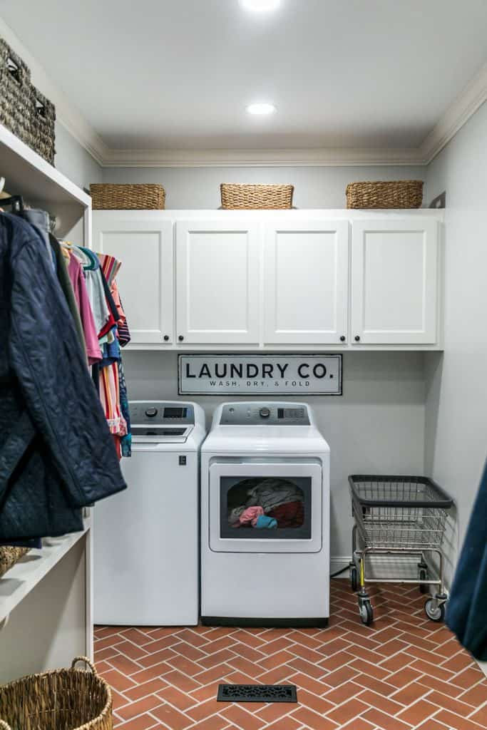 A spacious laundry room with brick patterned flooring, two washing machines, and white paneled hanging cabinets