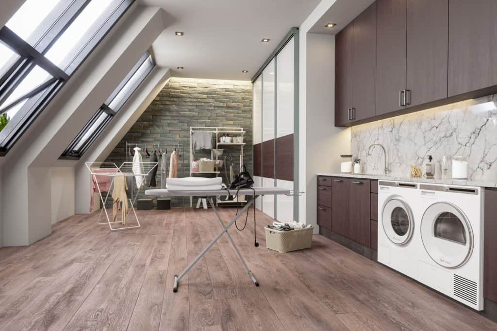 A spacious laundry room, wooden paneled cabinets, wooden flooring, and washing machines on the side