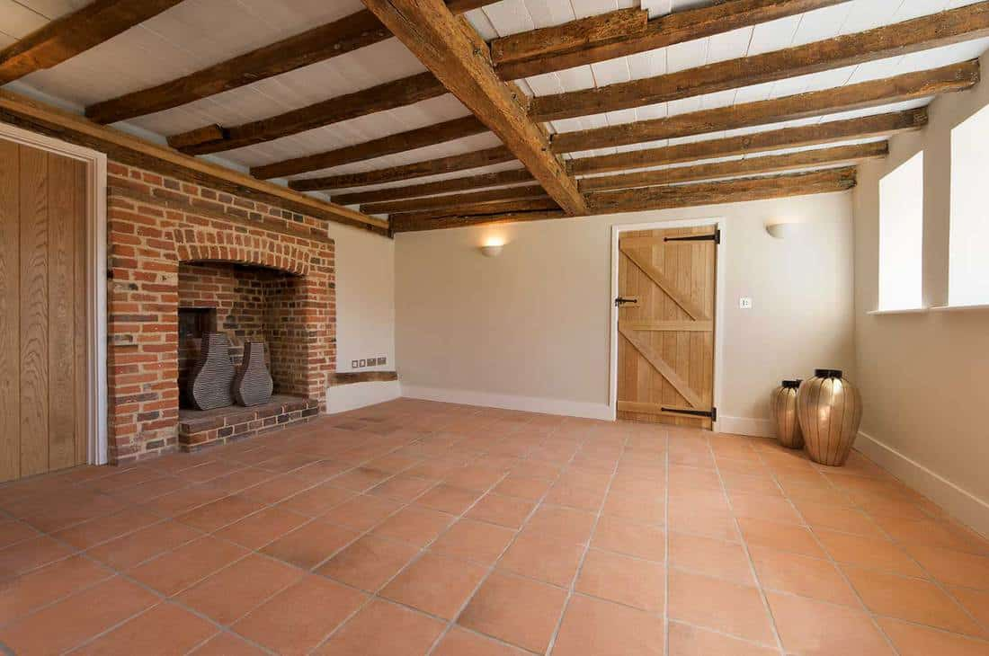 A terracotta tiled floor and inglenook fireplace of a newly restored country farmhouse