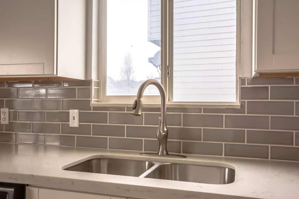 A warm and gray colored kitchen area with a double sink lavatory