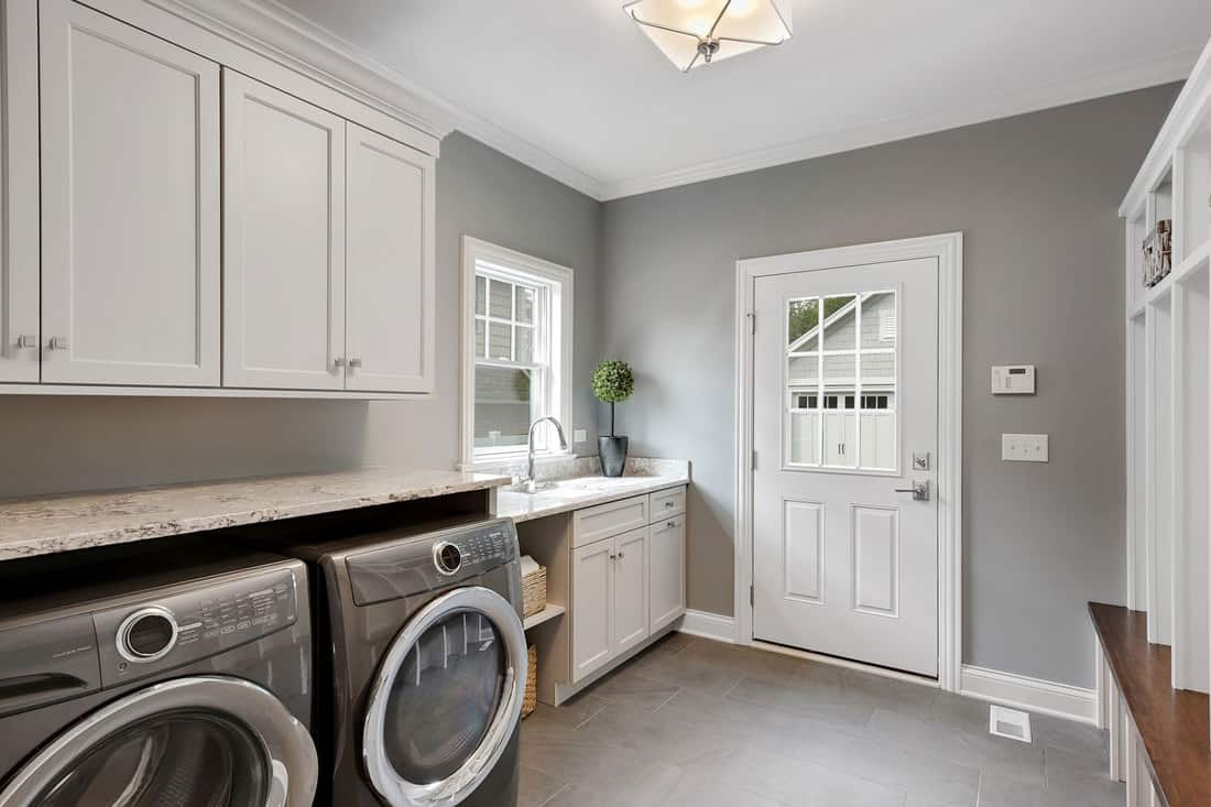 A washing room with gray painted walls, gray tiled flooring two washing machines with white painted hanging cabinets, 10 Great Laundry Room Light Fixture Ideas