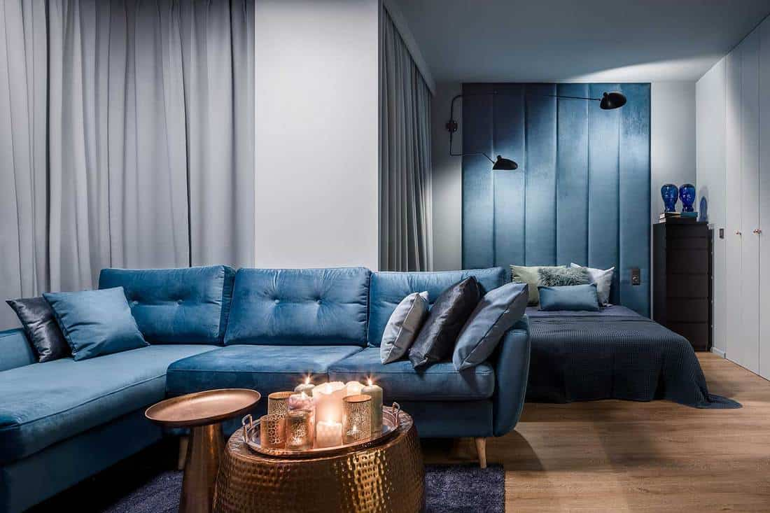 Amazing apartment in blue with corner sofa, copper coffee tables and open bedroom