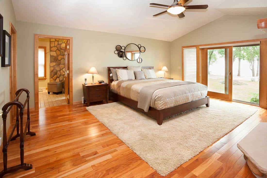 Amazing master bedroom suite with raised ceiling and hardwood floor