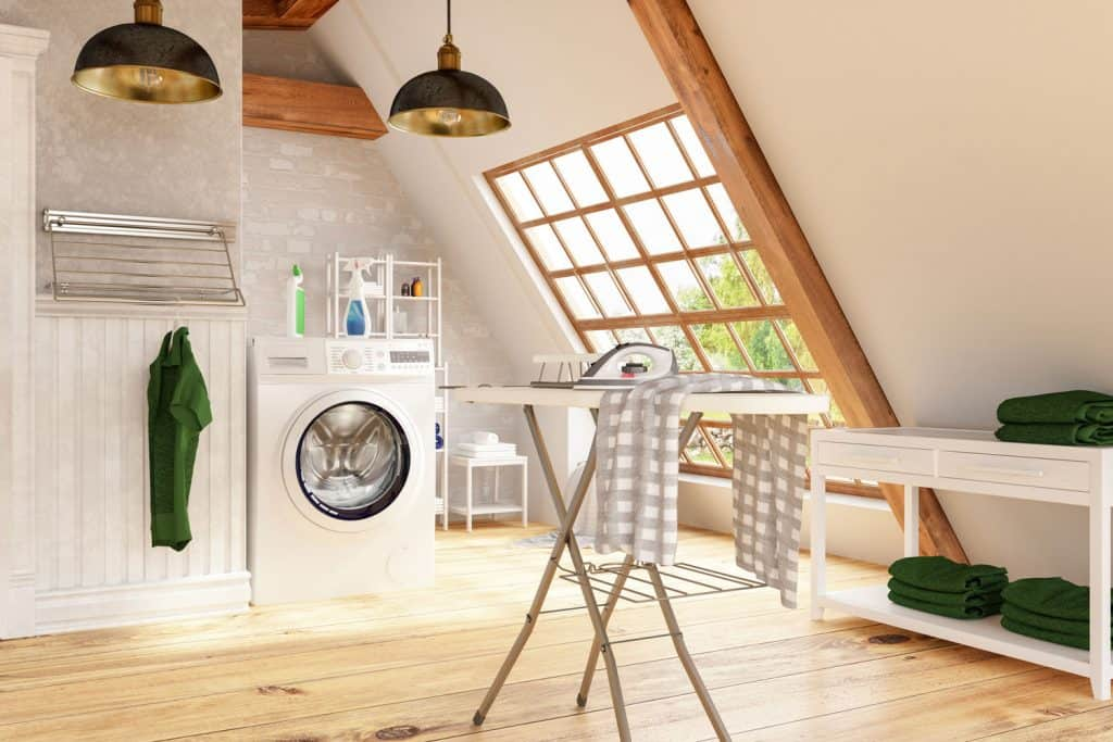 An attic washing room with white painted walls, protruding trusses, and wooden flooring