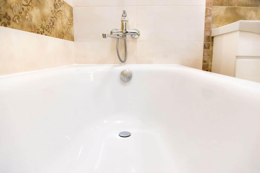 An up close photo of a white bathtub