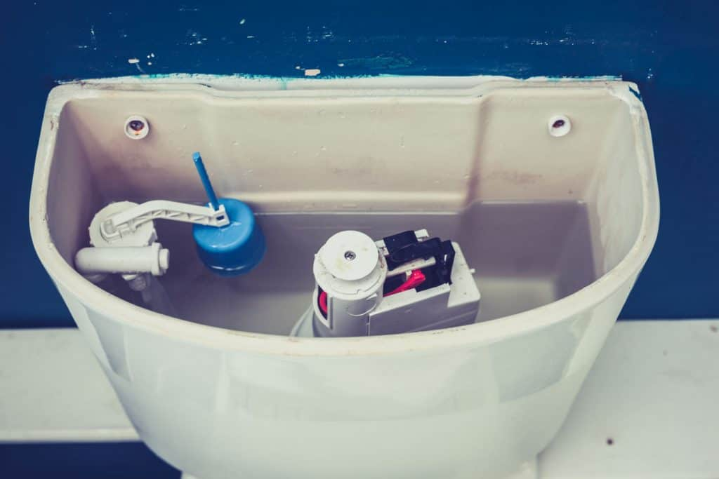 An up close photo of the inner mechanisms of a toilet