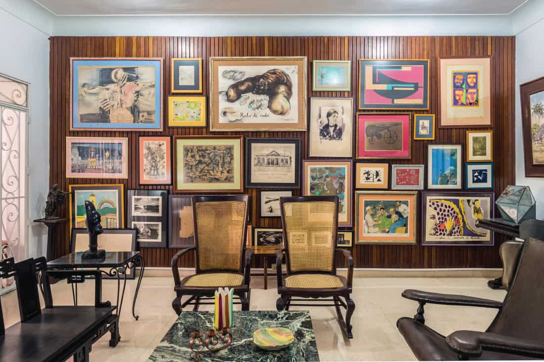 Art room featuring numerous paintings by Cuban artist of various styles and ages