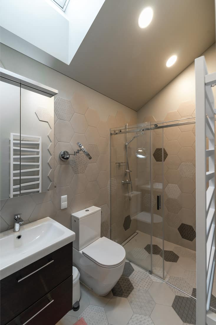 Bathroom in the attic. On the wall - towel radiator. Shower behind transparent partition. White toile. Room For A Shower And Not A Tub