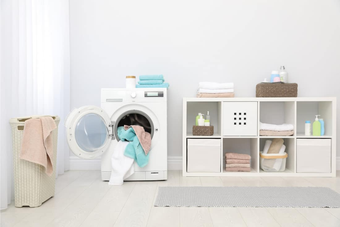 Bathroom interior with towels and washing machine. Cube Storage in White