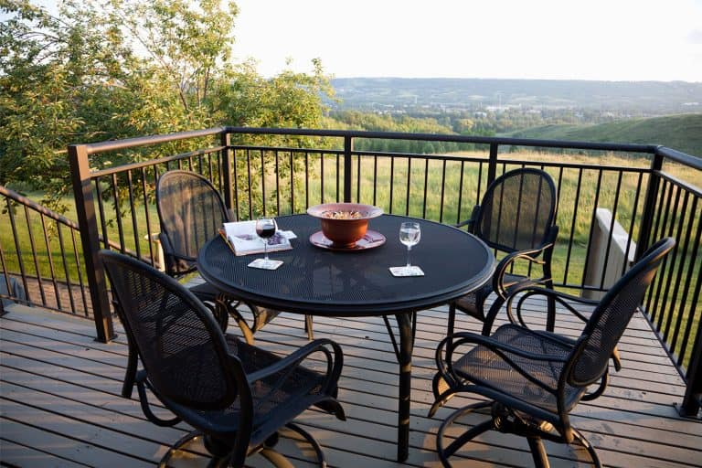 Beautiful sunlight evening. Black Wrought Iron patio furniture. Glass of red and glass of white white on table, What Type Of Outdoor Furniture Lasts Longest?
