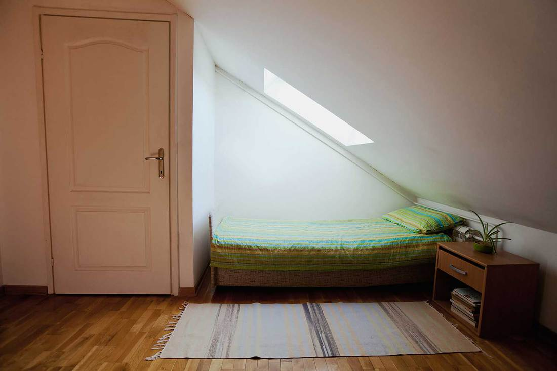 Bed with bedside table under the window in attic bedroom