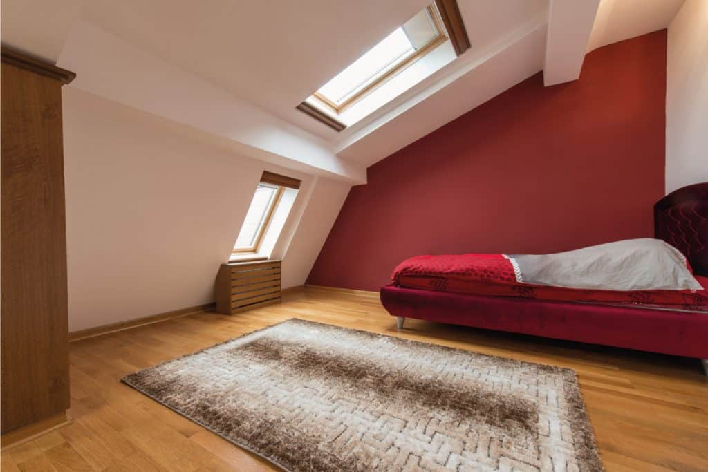 Bedroom interior in luxury red loft, attic, apartment with roof. Does An Attic Count As A Bedroom
