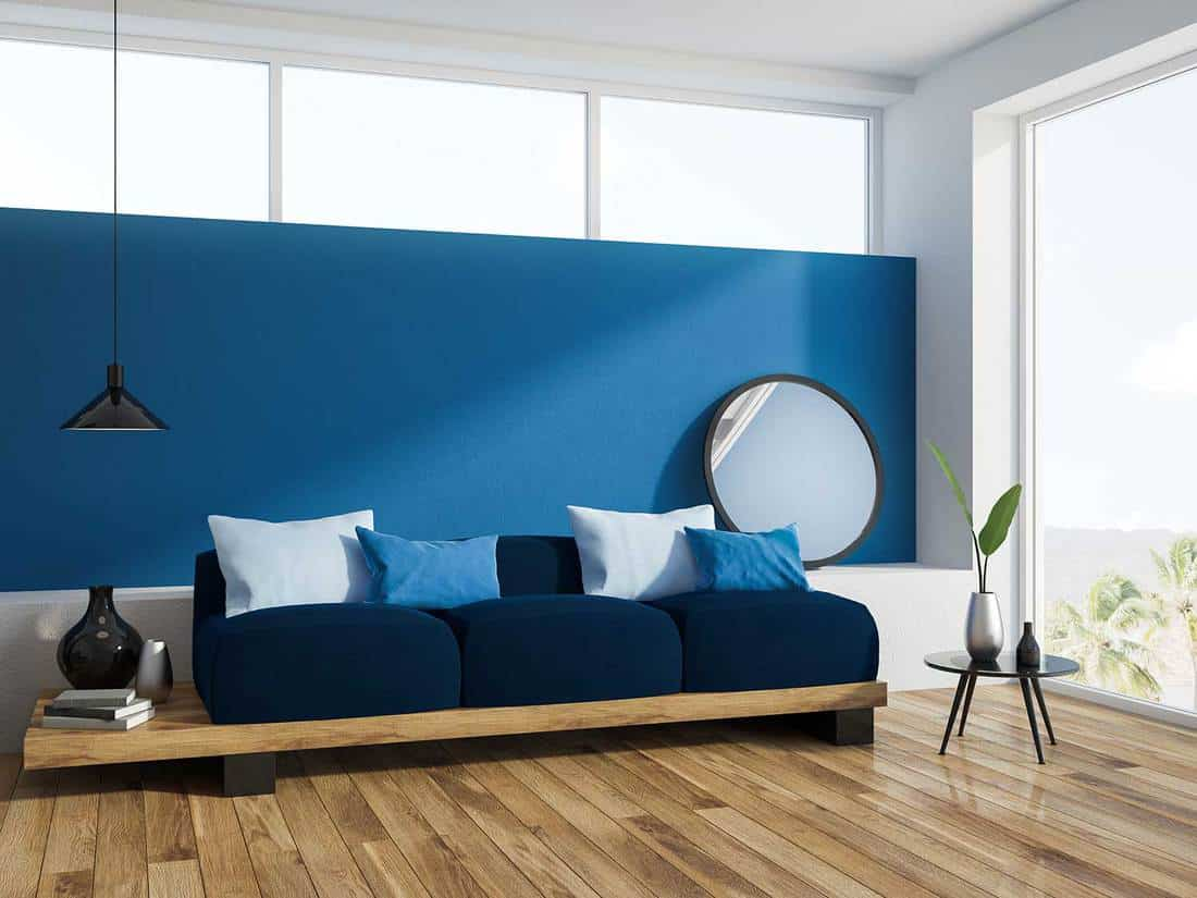 Blue living room corner with a wooden floor, a loft window and a long comfortable dark blue sofa with navy cushions on it