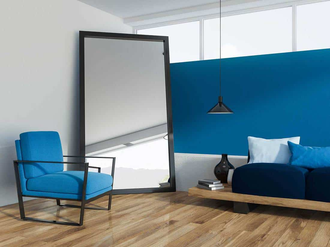 Blue living room corner with wooden floor, loft window, comfortable dark blue sofa with navy cushions, armchair and large mirror on the floor