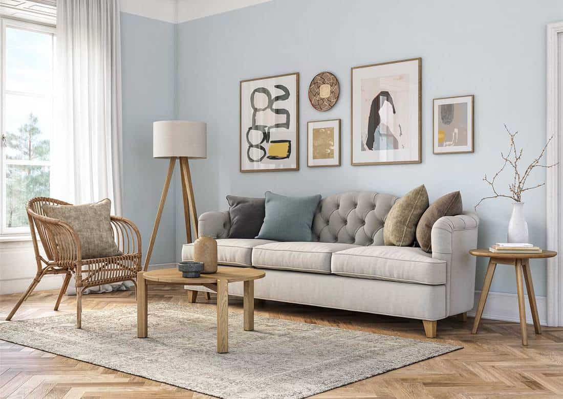 Bohemian living room interior with wooden furniture, sofa, parquet floor and light blue colored wall