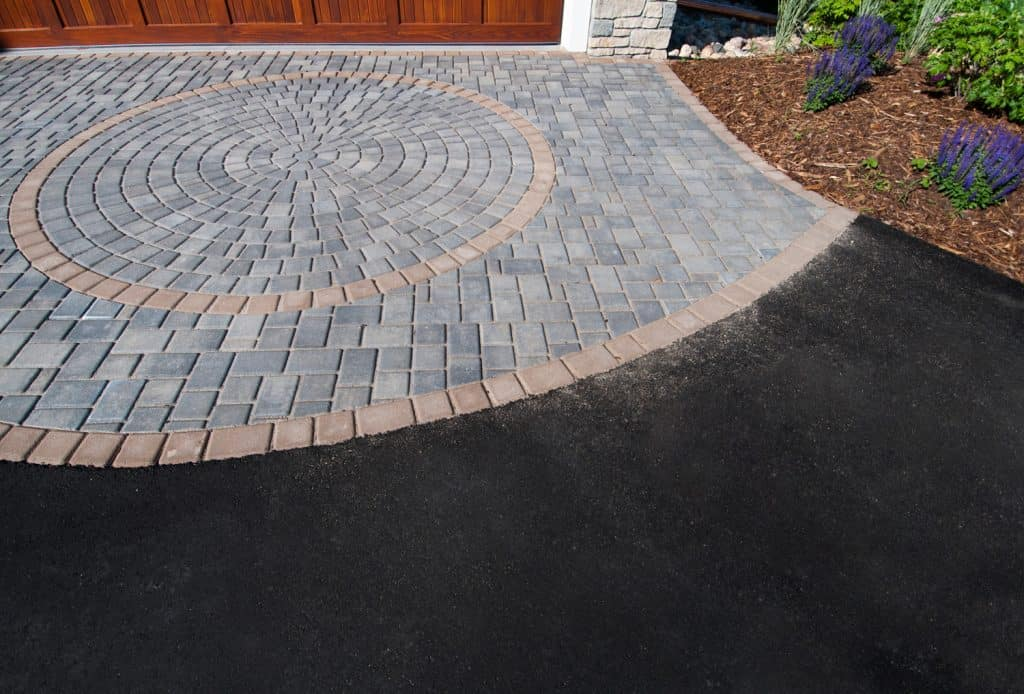 Brick Paver and asphalt driveway with wooden garage door and plant landscaping