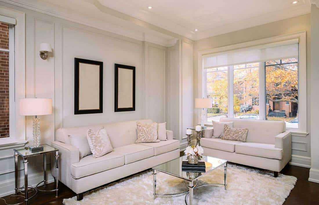 Bright interior living room in newly built North American private home with white sofas and carpet