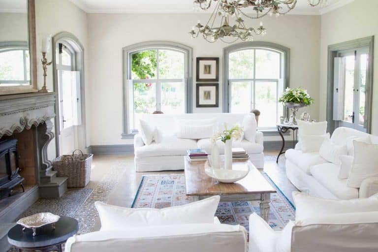 Bright living room interior with white sofa set, wooden coffee table, fireplace and carpet on floor, 15 Hamptons Style Living Room Ideas