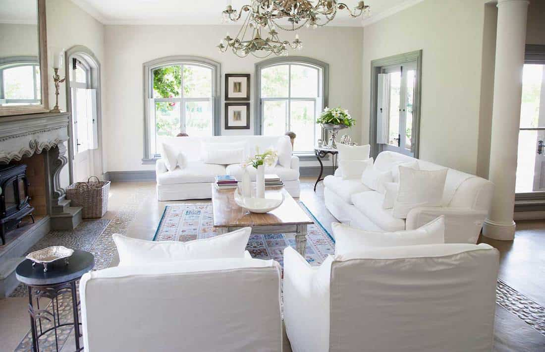 Bright living room with white sofa set, wooden coffee table, fireplace and carpet on floor