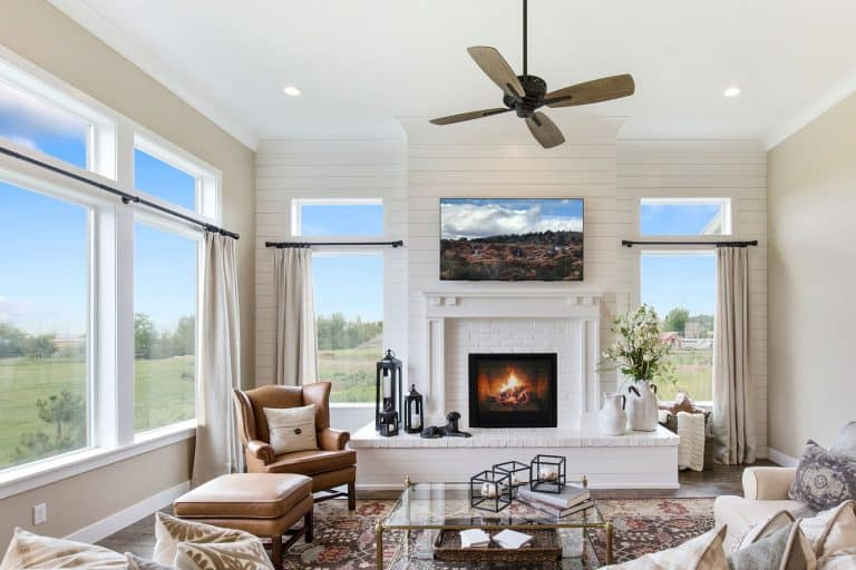 Ceiling fan hangs above gorgeous room with tall oversized windows, Can A Living Room Have No Windows?