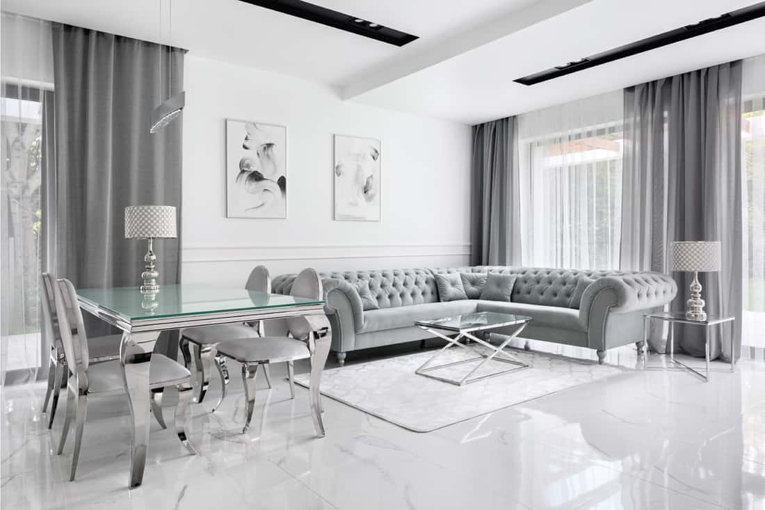 Charming and luxury living room in gray and white with glass table and glamour style corner sofa. white with light gray accents