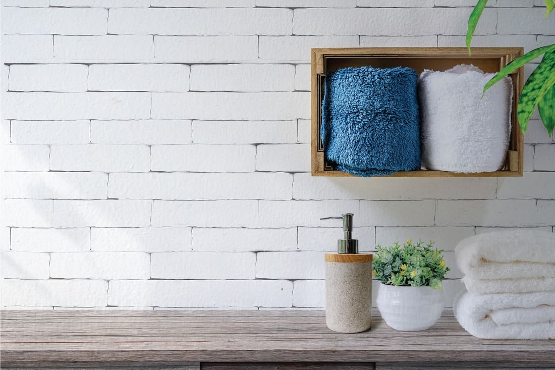 Clean towels with soap dispenser on shelf and wooden table in bathroom, white brick wall with bathroom shelf