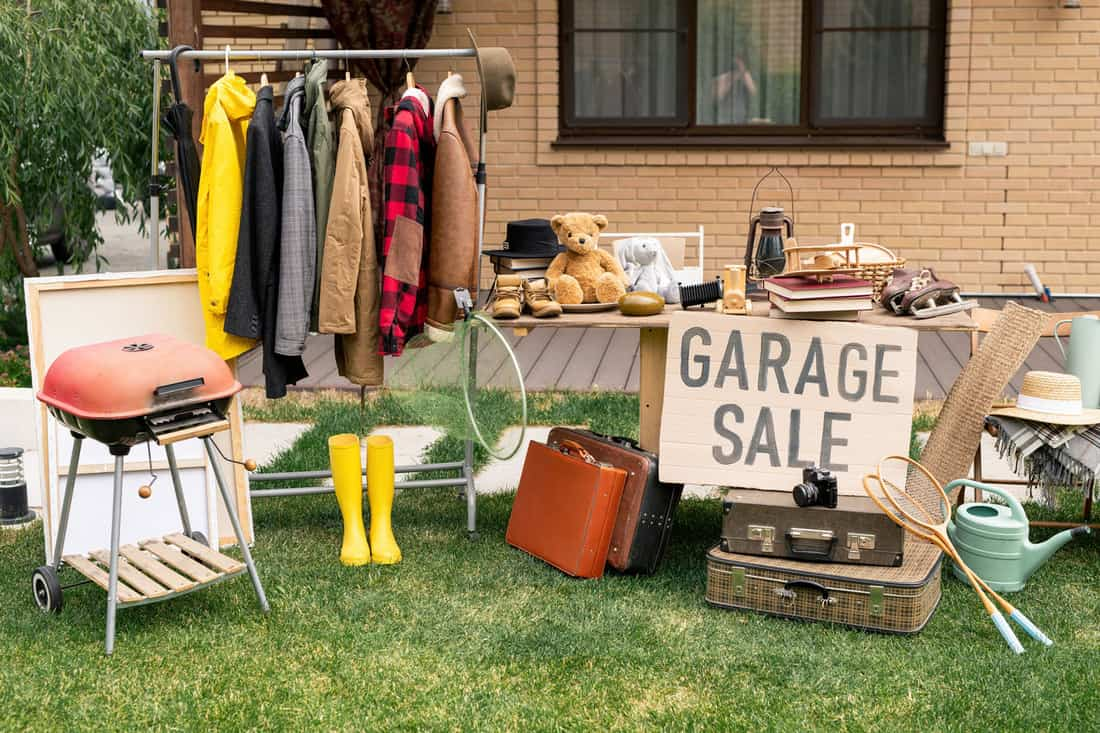 Clothes rack, old-fashioned suitcases, garden tools and interior goods selling at garage market in backyard