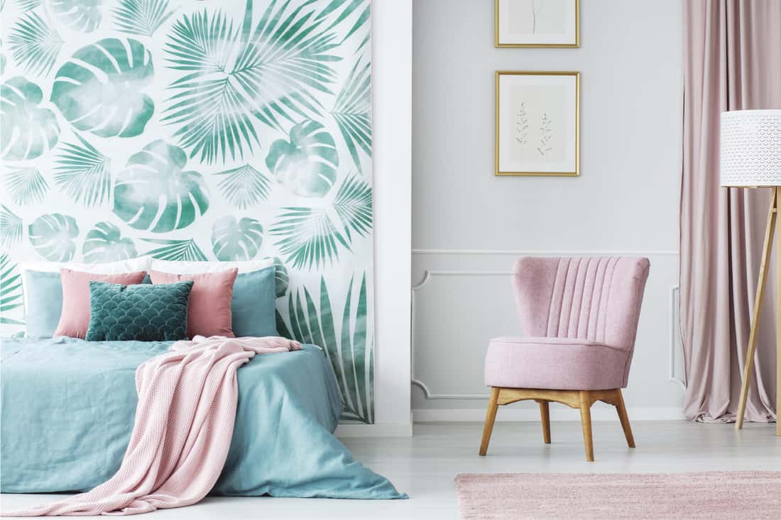 Comfortable pale pink upholstered chair in a cozy bedroom interior with double bed and green and leaves decorations
